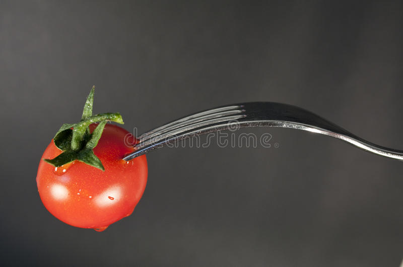 Tomato and fork. Particular of tomato and fork stock photos