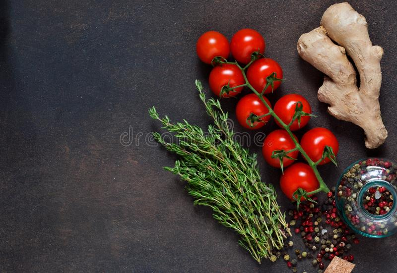 Tomato, ginger and a variety of spices on a dark background royalty free stock photos