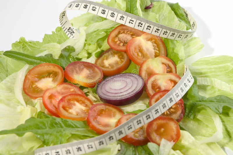 Tomato heart 1. Tomato slices, on a bed of lettuce, in a heart shape with metric tape measure stock photography