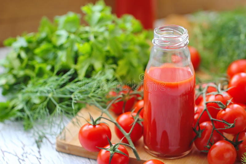 Tomato juice in bottles. And fresh vegetables royalty free stock images