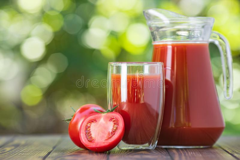Tomato juice in glass and jug stock photos