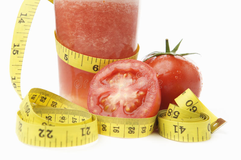 Tomato juice with measuring tape royalty free stock image