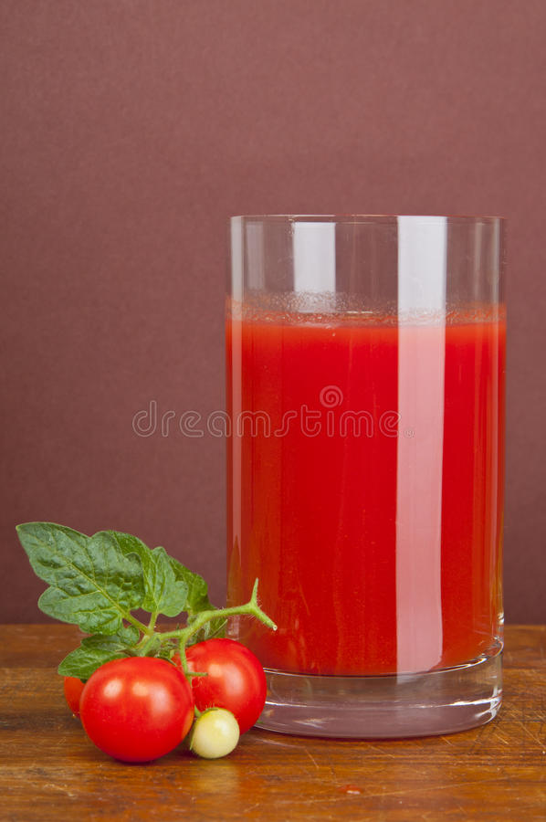 Tomato juice. In pitcher with tomatoes on wooden table stock image