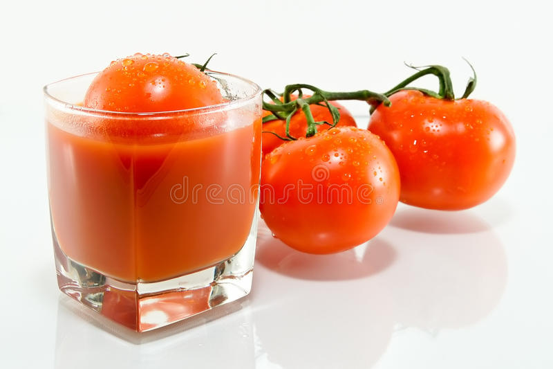 Tomato juice and tomato. Glass of tomato juice next to the red ripe tomatoes stock image