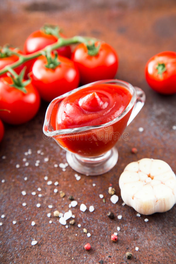 Tomato ketchup sauce with garlic, spices and herbs with cherry t. Omatoes in a glass bowl, selective focus royalty free stock photo