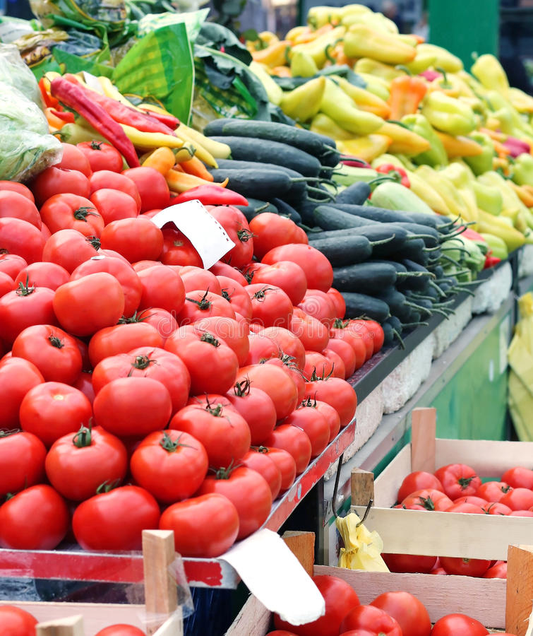 Tomato market stall. Large pile of tomatoes and other vegetables on market stall royalty free stock image
