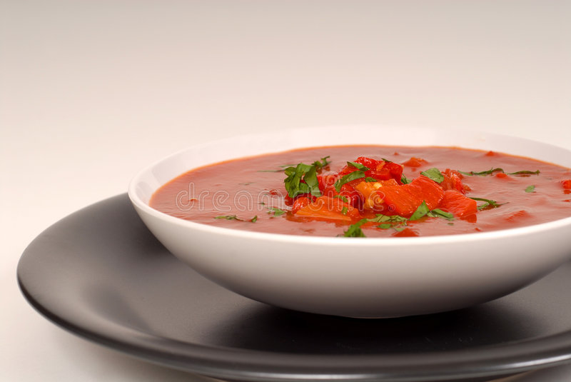Tomato, red pepper, basil soup in white bowl with light gray background royalty free stock photos