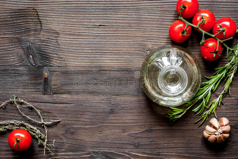 Tomato, rosemary and garlic on dark wooden background top view.  royalty free stock images
