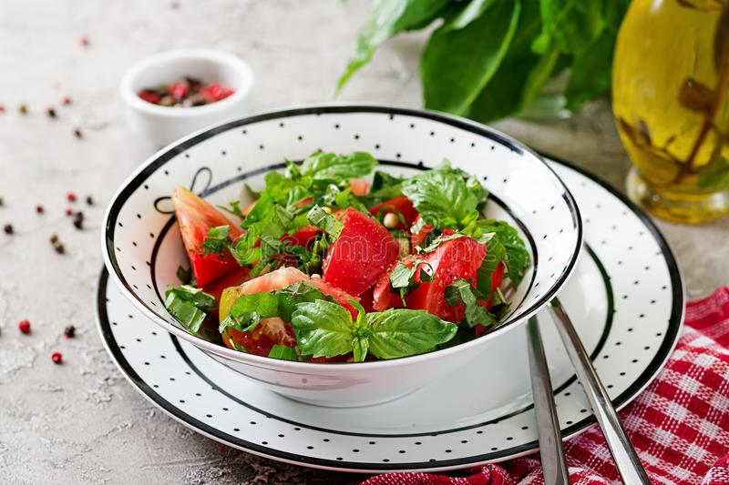 Tomato salad with basil and pine nuts in bowl - healthy vegetarian vegan diet organic food appetizer.  royalty free stock image