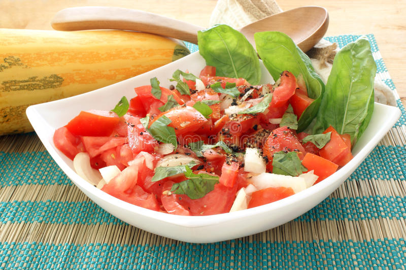 tomato salad in bowl with onion and basil stock photos