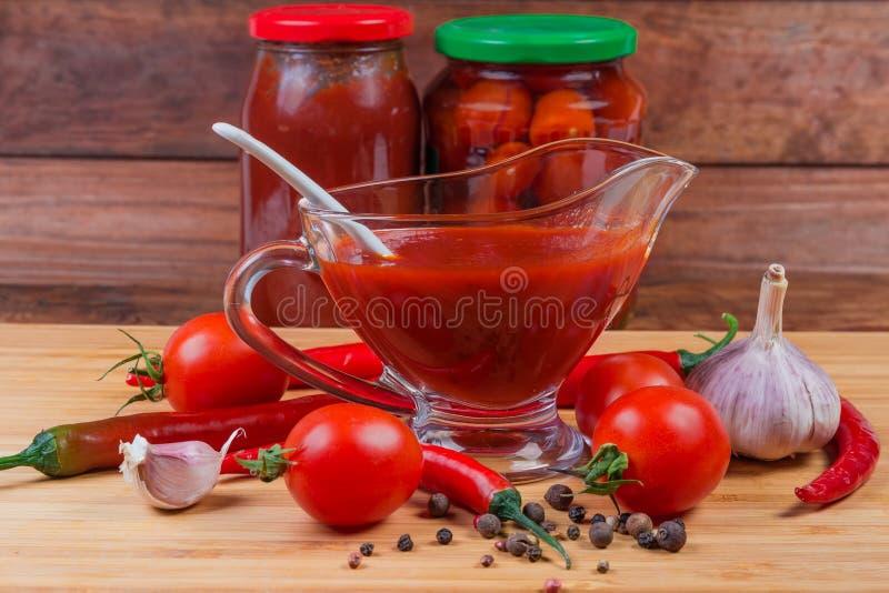 Tomato sauce in glass gravy boat, ingredients, canned tomato products. Tomato sauce in the glass gravy boat next to several raw ingredients for its preparation royalty free stock image