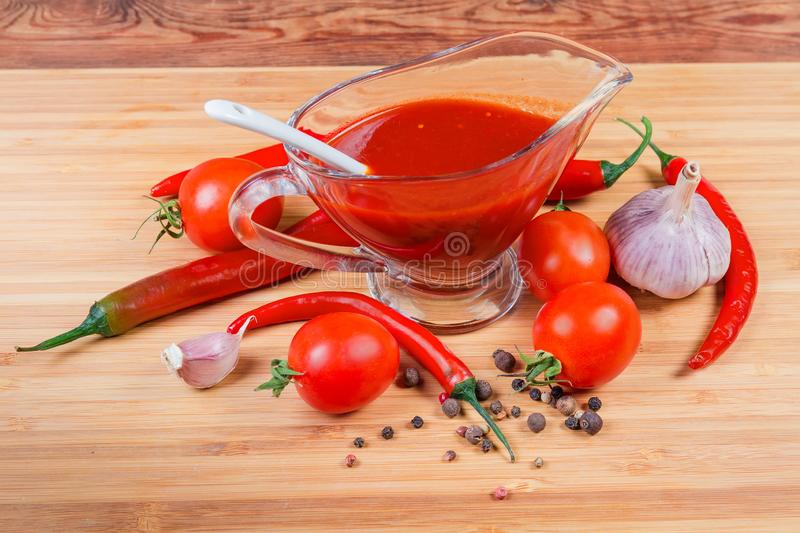 Tomato sauce in glass gravy boat among of its ingredients. Tangy tomato sauce in the glass transparent gravy boat with white ceramic spoon next to several raw royalty free stock image