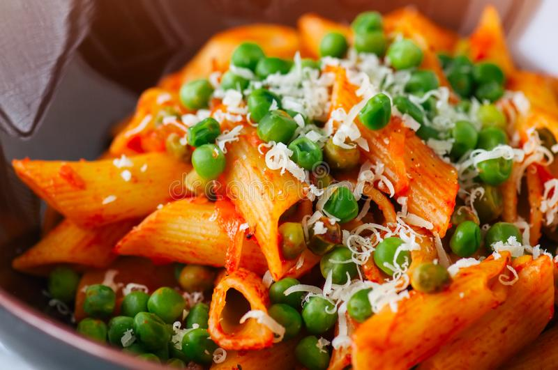 Tomato sauce and green peas penne pasta in a plate on a white st royalty free stock photos