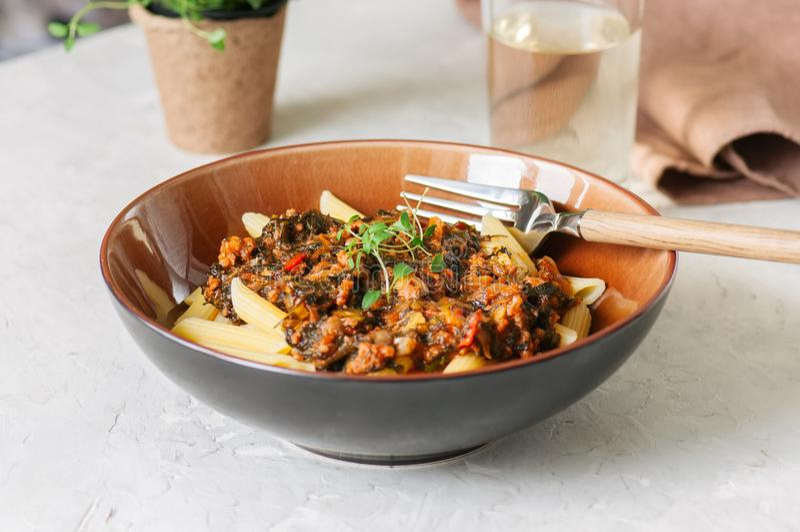 Tomato sauce ground beef pasta on a white stone background. Tone royalty free stock image