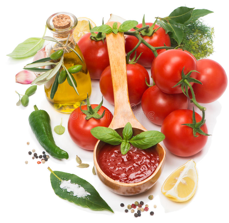 Tomato sauce and ingredients. Tomato sauce in a wooden spoon and fresh ingredients on a white stock image