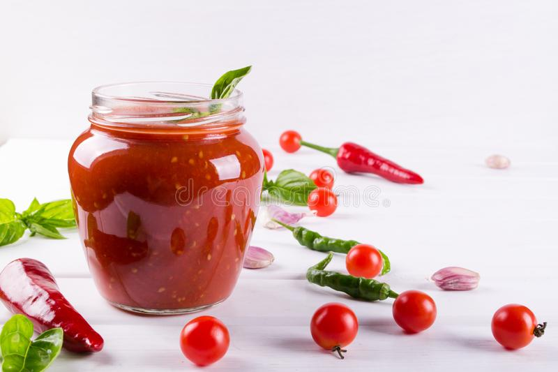 Tomato sauce, ketchup in glass jar and ingredients. On a white background royalty free stock photography