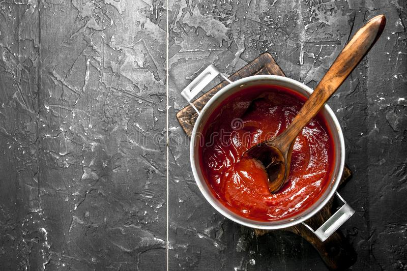 Tomato sauce in a pot with a wooden spoon. On black rustic background stock photo