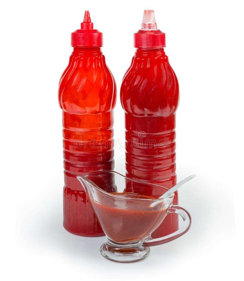 Tomato sauce in two plastic bottles and in gravy boat. Tomato sauce in two red plastic bottles and in glass gravy boat with small spoon on a white background stock image
