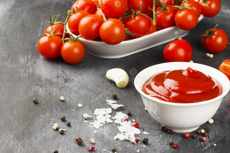 Tomato sauce in white bowl, spice and cherry tomatoes on a dark. Background. Copy space. Food background stock photos