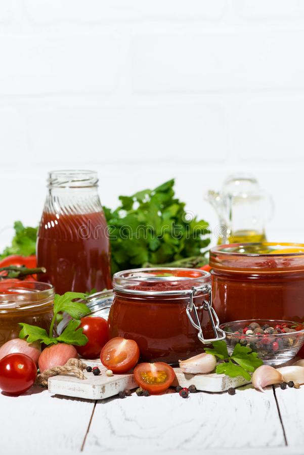 Tomato sauces, pasta and fresh ingredients on white wooden background, vertical royalty free stock photos