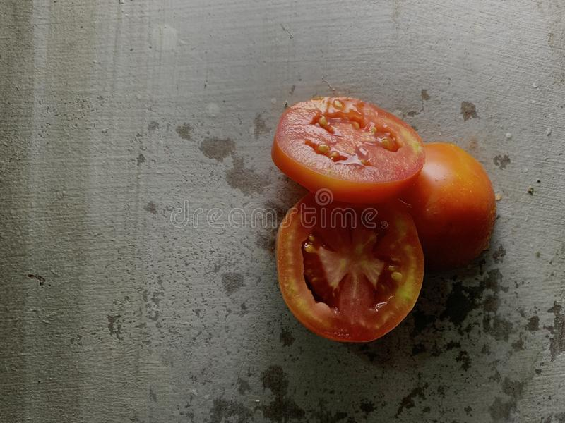 Tomato sliced on rustic background in studio, Food Photography. Overhead view of fresh red tomato sliced on rustic background in studio, Food Photography stock photography