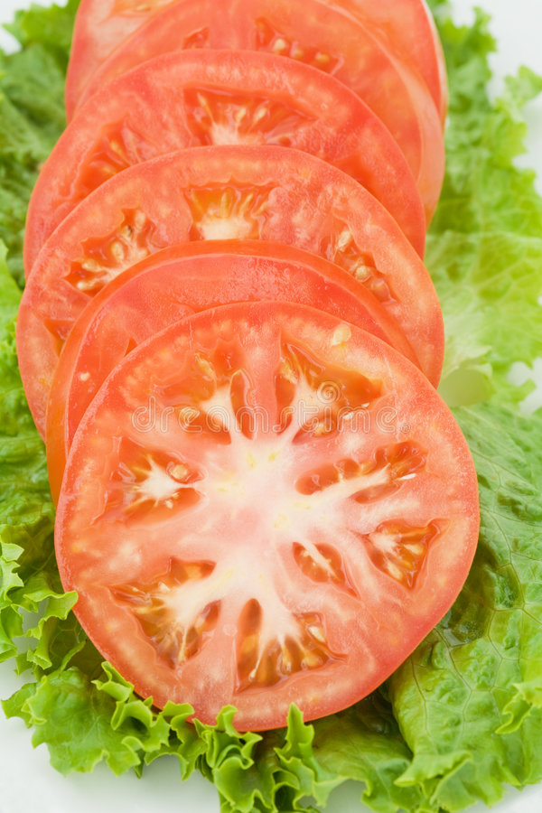 Tomato Slices On Green Stock Photo