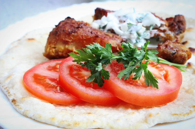 Tomato slices. Parsley and tandoori chicken royalty free stock photography