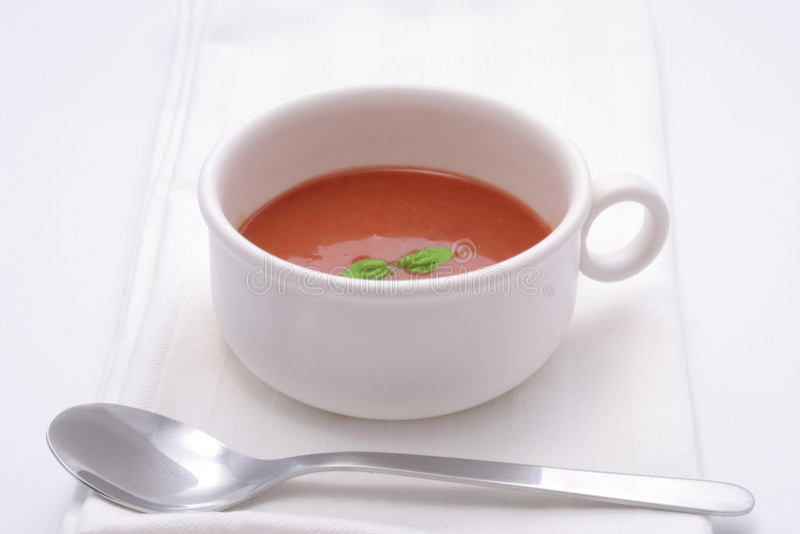 Tomato soup with basil garnish stock photos