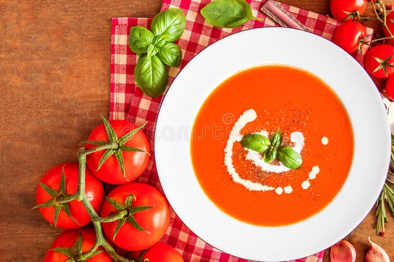 Tomato Soup composition with fresh tomatoes, basil leaf and garlic on a wood table, view from above. Vegetarian Autumn Food royalty free stock images