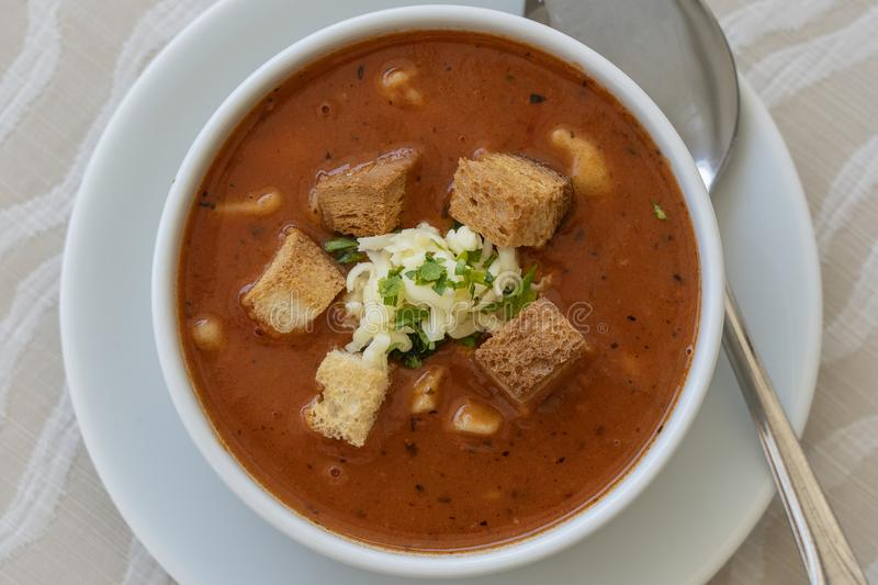 Tomato soup with croutons, cheese and fresh parsley, closeup stock images