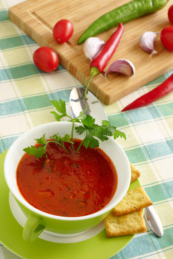 Tomato soup in a green bowl. Tomatoes, pepper and garlic on a cutting board royalty free stock photos