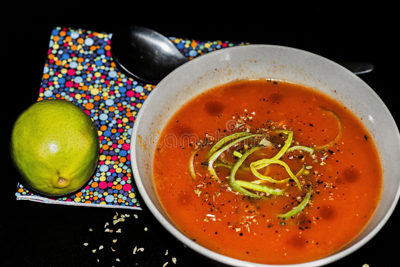 Tomato soup. Nice red tomato soup with sliced leek, whole lime, spoon and small varicolored spotted table setting on black background with herb leaves royalty free stock image