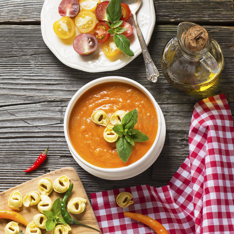 Tomato soup puree. Fragrant homemade tomato soup puree with tagliatelle on a dark wooden background with bright colored mini tomatoes, hot pepper, olive oil stock images