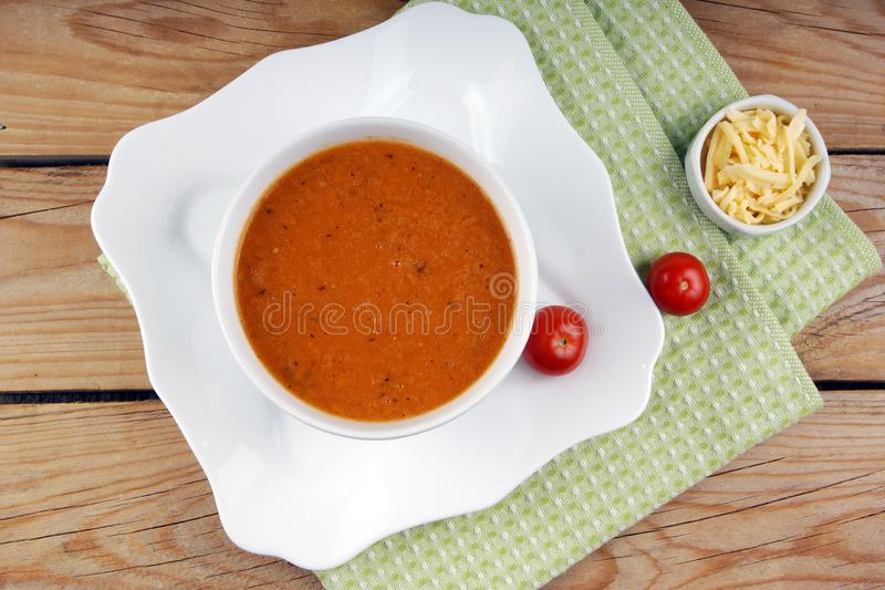 Tomato soup puree poured into a white plate, decorated with cherry tomatoes, grated cheese and a green napkin.  royalty free stock image