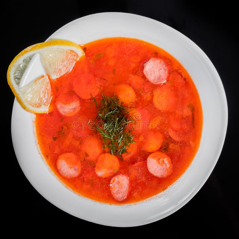 Tomato soup with smoked sausages and herbs in bowl, isolated on black background, healthy food. royalty free stock photos