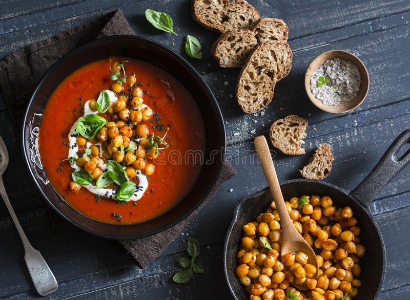 Tomato soup with spicy fried chickpeas on a dark wooden table, top view. Healthy vegetarian food stock photos