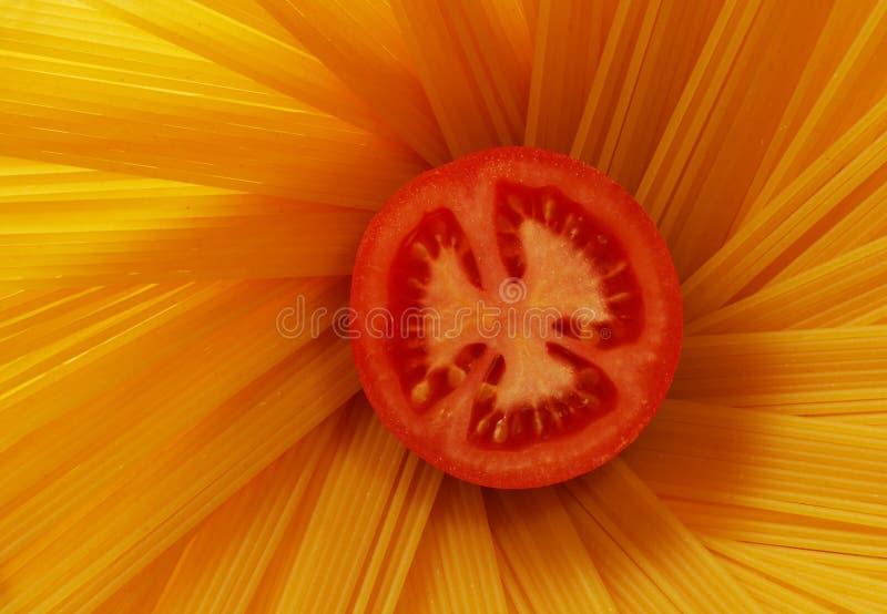 Tomato and spaghetti. A sliced tomato and some spaghetti royalty free stock photos