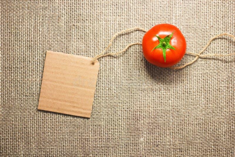 Tomato vegetable and price tag on sacking background texture royalty free stock photos