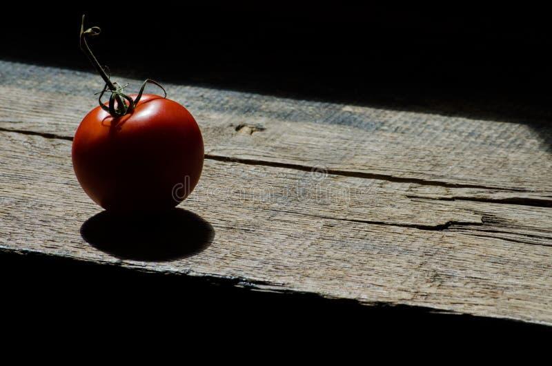Tomato on wooden plank stock image