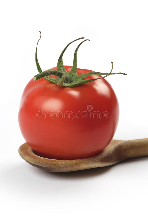 Tomato in wooden spoon royalty free stock images