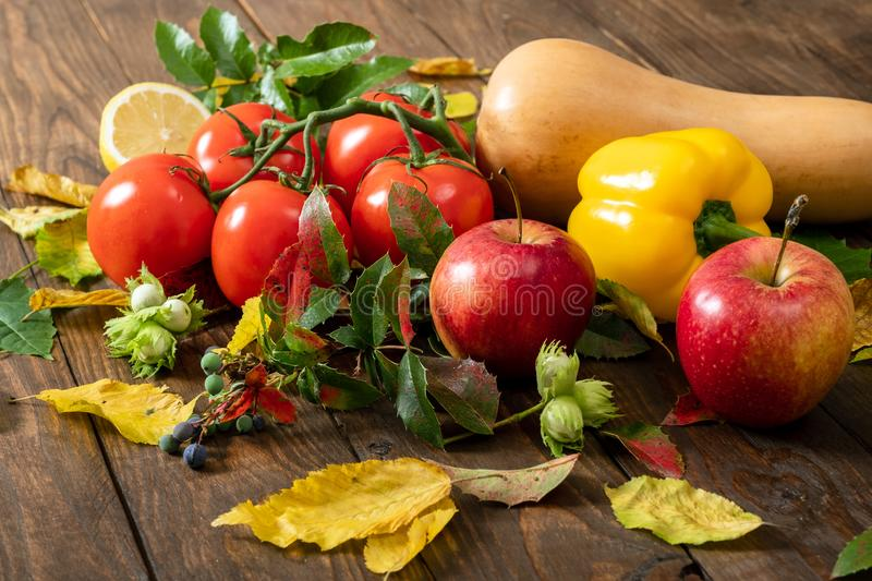 Tomato, yellow pepper, squash, hazel nut and autumn leaves closeup. Still life food, autumn concept. Vegetables and fruits on royalty free stock photo