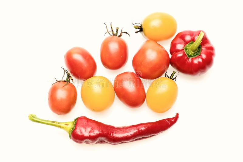 Tomato of yellow and red colors with chili peppers. Isolated on white background. Tomato berries and peppers in close up. Summer harvest vegetables with bright royalty free stock photo