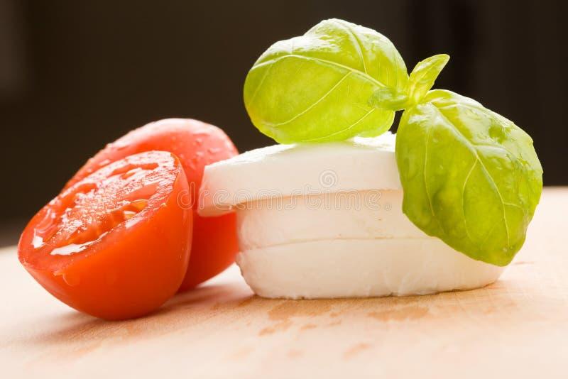 Tomatoe e Mozzarella na placa de estaca imagem de stock