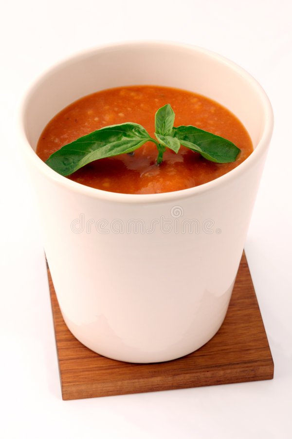 Tomatoe soup with basil in white cup stock photo