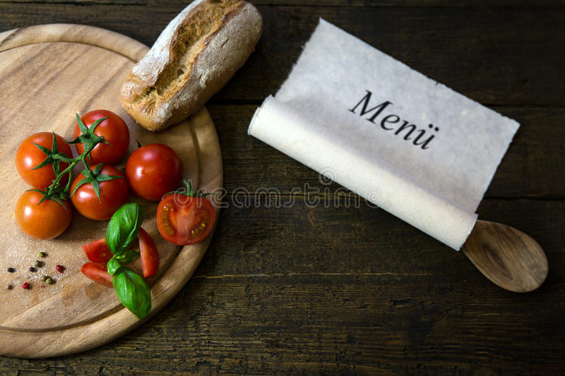 Tomatoes, basil and bread on a wooden table, scroll with word Me royalty free stock photo