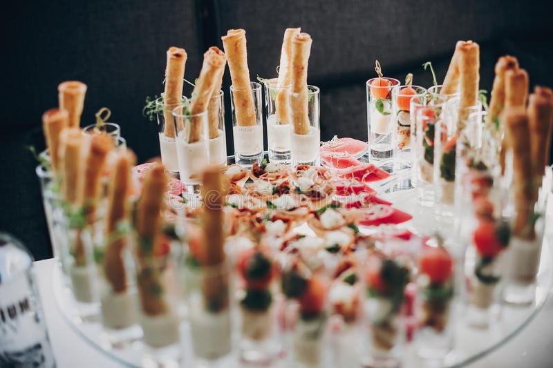 Tomatoes, basil,cheese,prosciutto, greenery and bread appetizers on table at wedding or christmas feast. Luxury catering concept. royalty free stock image