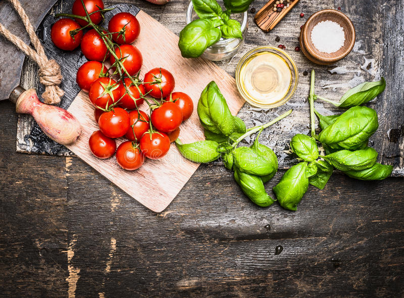 Tomatoes and basil with olive oil on wooden cutting board on rustic background, top view stock image