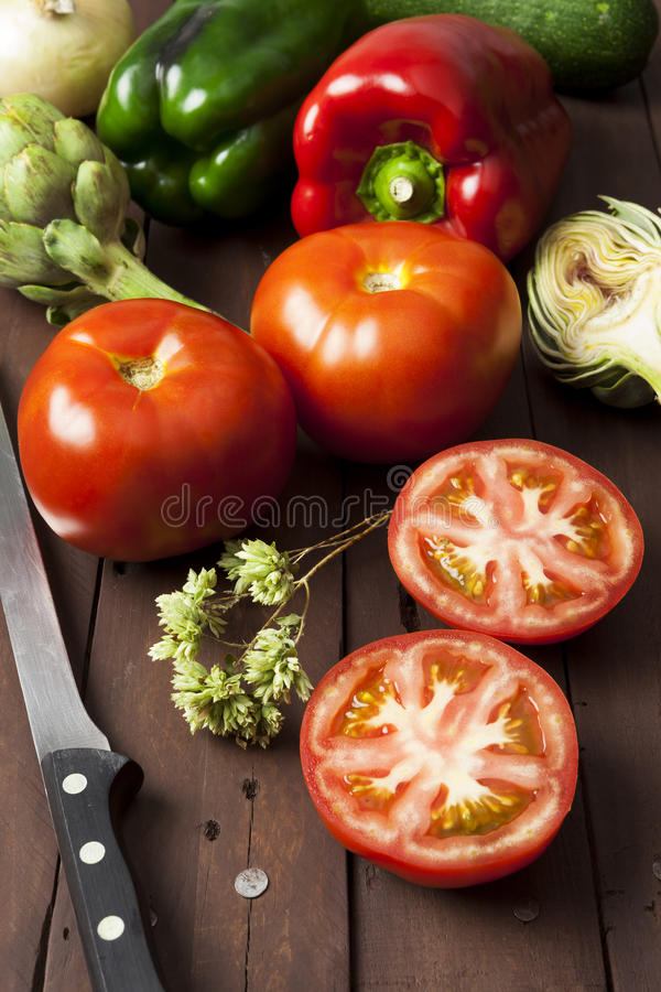 Tomatoes, bell peppers and artichoke with knife. On a brown wooden table. Vertical composition royalty free stock photography
