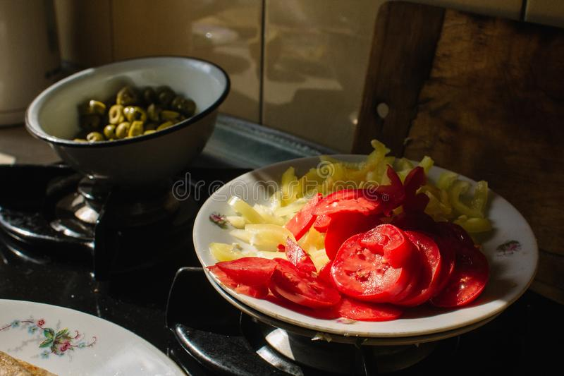 Tomatoes, bell peppers and green olives in the kitchen. Ingredients for pizza. Tomatoes, bell peppers and green olives in the sun in the kitchen. Ingredients for stock photos
