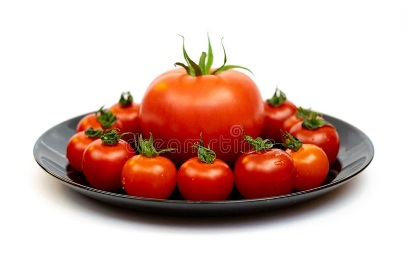 Tomatoes in a black plate isolated on white background. Composition of red tomatoes on a white background. royalty free stock photo